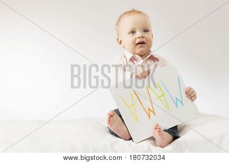 Open-mouthed baby boy holding big nameplate with flipped over sign Mama. Postcard for Mothers day.