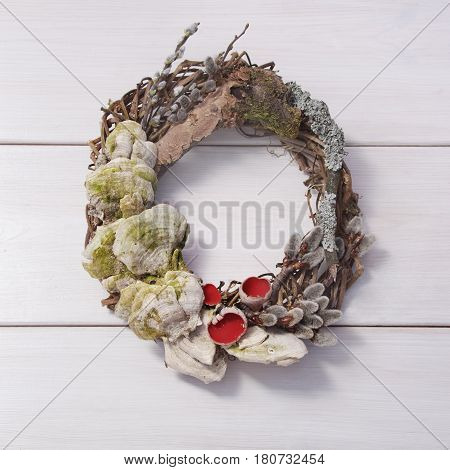 Wreath with willow twigs wood mushrooms and sarcophagus on a white wooden background