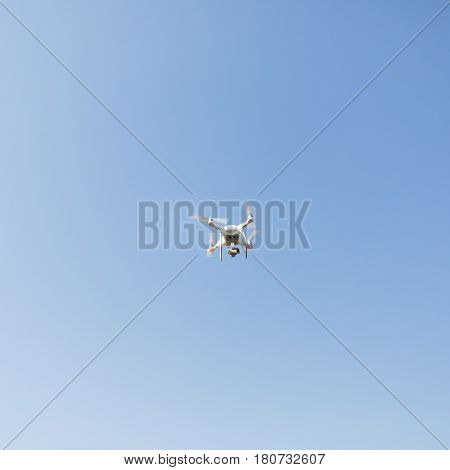 Copter against the background of a cloudless blue sky. A drone with a high-resolution camera.