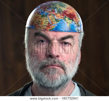 MOSCOW RUSSIA - MARCH 24,2017: A bearded man put cap-earth hemisphere on his head