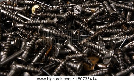 techno backgrounds - black oiled Bunch of screws on a dark grey cardboard
