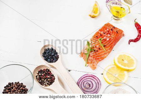Delicious portion of fresh salmon fillet with aromatic herbs, spices and vegetables - healthy food, diet or cooking concept. Top view and copyspace.