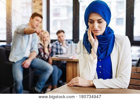 Multicultural society. Pleasant beautiful young muslim woman sitting at the table in the cafe while her mates abusing her