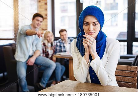 I need justice. Pleasant beautiful muslim woman sitting at the table while her groupmates pointing her while abusing