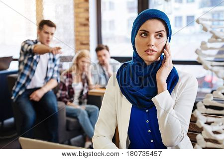 Spotlight of gossips. Pleasant muslim student sittign at the table and talkign on smartphone while her groupmates abusing her
