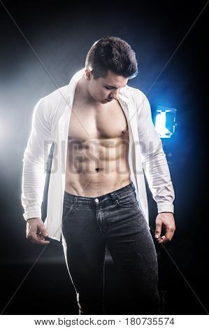 Confident, attractive young man with open shirt on muscular torso, ripped abs and pecs. On dark background with spotlights behind him