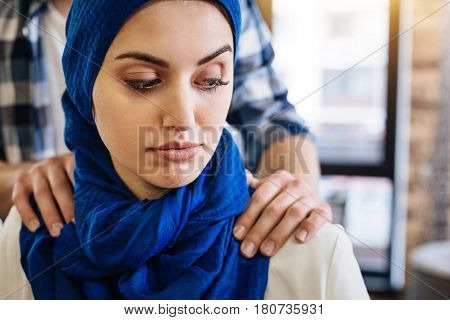 Dont touch me. Pleasant muslim woamn sitting while representative of another religious group herassing her