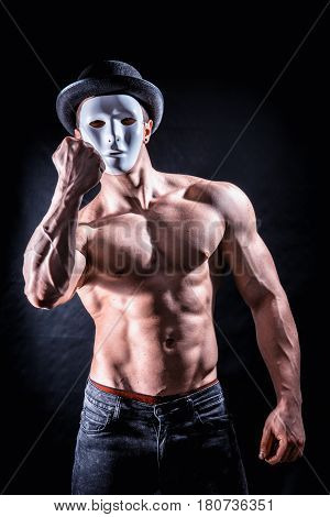 Shirtless muscle man with creepy, scary mask being aggressive and violent, on black background