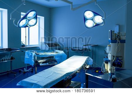 Various equipment at operating-room. Switched on lamps are above medical table