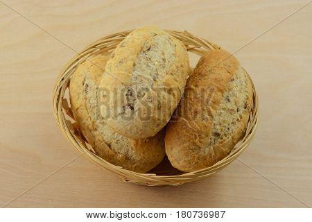 Wholegrain hard rolls in wooden wicker bread basket