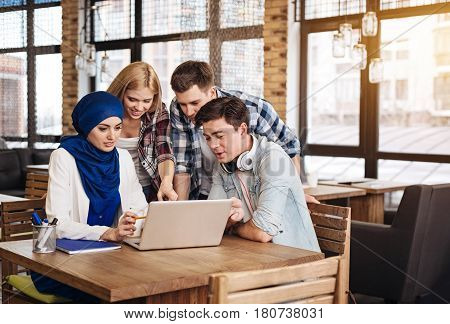 Involved in cooperation with everyone. Cheerful delighted international students looking at the screen of the laptop while studying together