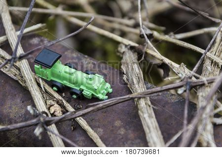 Green steel toy train in a background full of brambles conceptual photo