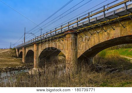Rural Stone Road Bridge Crossing River With Beautiful Landscape saturated photo