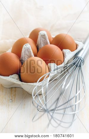 Box With Eggs And Whisk On White Wooden Table.