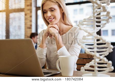 Involved in network. Cheerful delighted yung woman sitting in the cafe and surfing the Internet while reading articles about genetics
