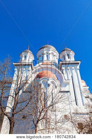 Romanian orthodox white church against blue sky