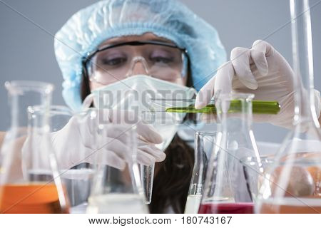 Researching and Science Concepts. Female Laboratory Staff in Facial Mask And Protective Gloves Conducting Experiment with Liquids in Flasks in Lab. Horizontal Image Composition