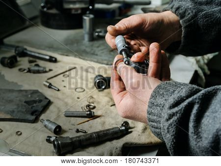Mechanics repairing a diesel injector. Workers hands is holding micrometer. A man measures the thickness of spare parts to the injector. poster