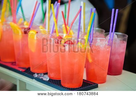 Non-alcoholic cocktails. Fruit and berry cocktails with colored tubules. Fitness Bar. The barman prepares fruit cocktails.