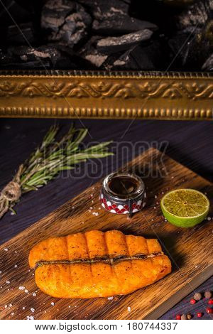The stake from fillet of a salmon fried on coals with sauce and spices