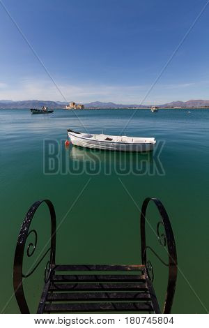 Pier Steps Traditional Fishing Boats and Bourtzi Fortress in the distant background in Nafplion Greece- portrait photo