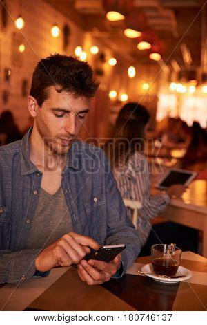 Unshaven Millennial Texting In A Restaurant