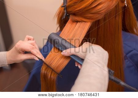 Hairdresser Makes Hairstyle Girl With Long Red Hair In A Beauty Salon. Straightening Hair Ironing. P