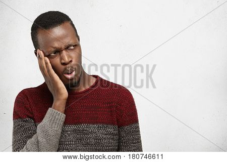 Portrait Of Handsome Afro American Male Student Or Customer Frowning, Looking Sideways With Shocked