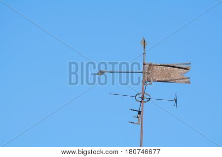 Old Rusty Metal Weather Vane with Clear Blue Sky