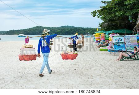 Koh Samet, Thailand - October 29, 2016: Thai Beach Sellers Crossing The Beach To Offer Their Product