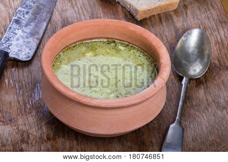 Traditional Polish sour gherkin soup served in a clay bowl.