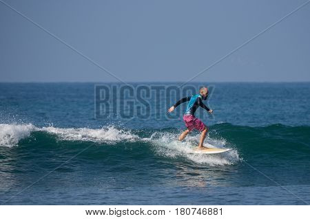 WELIGAMA SRI LANKA - JANUARY 06 2017: Unidentified man surfing on a large wave on Weligama beach on the coast of Indian ocean - is the best surf paradise in Sri Lanka