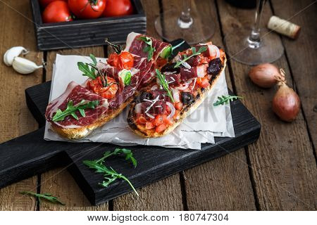 Spanish tapas with slices jamon serrano, salami, olives and cheese cubes on a wooden table. Spanish cuisine.