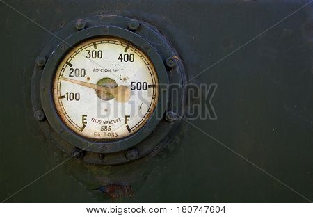 Fluid measure gauge for a train secured in place on a metal plate using nuts and bolts. Gauge measuring up to 585 gallons. With space for text.