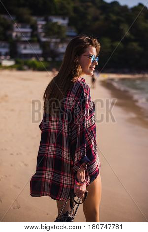 Summer lifestyle portrait of young pretty girl with sportive tanned body, walking to the beach of tropical island. Wearing checkered t-shirt and stylish sunglasses. With small beach bag.