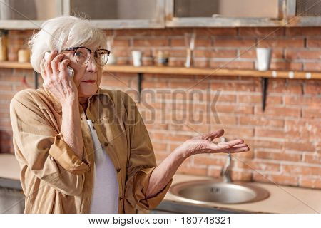 Portrait of surprised old woman is speaking by smartphone. She is standing in kitchen and gesturing with misunderstanding