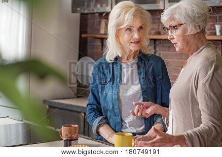 Two female pensioners are enjoying talk at the cup of tea. They are standing in kitchen and smiling