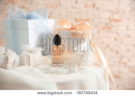 Table with gift boxes and perfume for wedding day