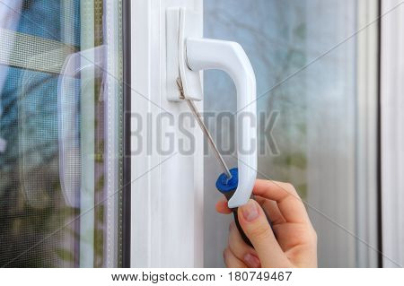 Dismantle the handle on a pvc window using a screwdriver close-up of a hand with a tool.