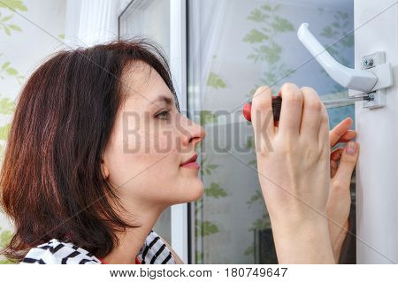 Young woman unscrews the fixing screws of the window handle.