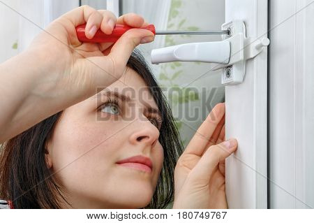 A young woman mounts a window limiter on the frame she tightens the bolt using a screwdriver.