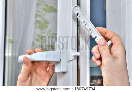 Installation of the opening limiter on the pvc window close-up.