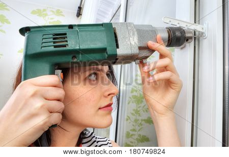 The girl makes fixing holes under the window limiter using an electric drill.