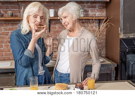 That is very delicious. Cheerful old woman is enjoying sweet food prepared by her friend. Senior lady is looking at her with happiness and smiling