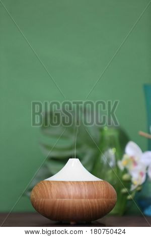 Aroma oil diffuser on blurred color background