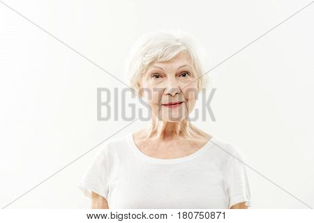 Waist up portrait of happy old woman standing and smiling. She is looking at camera with joy. Isolated on background. Healthy beauty concept