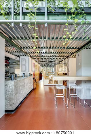 Loft style cafe with light walls and corrugated metal ceiling. There is a bar with a concrete rack, wooden table with benches, rack with white chairs, colorful doors, plants, signboards, lamps.