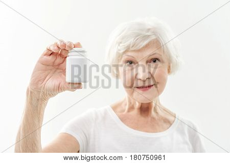 Take vitamins and be healthy. Cheerful mature woman is showing jar of pills to camera and smiling. Focus on medicine. Isolated