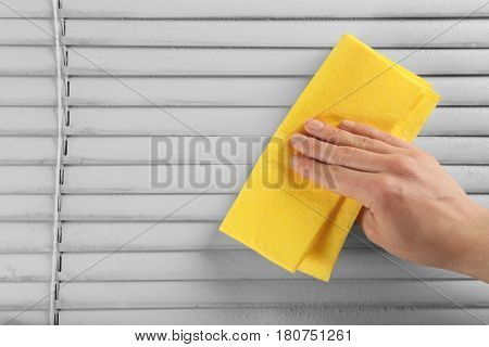 Human hand cleaning dirty window blinds, closeup