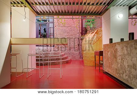 Stylish cafe in a loft style with a brick wall, white columns, red floor and corrugated metal ceiling. There are wooden and concrete racks, chairs, decorative pavilion, entrance glass door, stair.